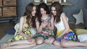 As amigas passam o tempo junto Fotos de observação do riso das meninas no telefone celular vídeos de arquivo