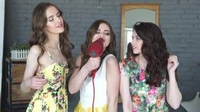 As amigas têm o divertimento e cantam-no no secador como em um microfone Três meninas atrativas enganam ao redor e dançam Movimen filme