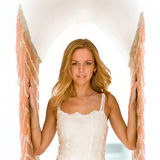 As angel. A girl stands high in the doorway of brick gallery and white ceiling arches are closed behind her like the wings of an angel Royalty Free Stock Photography