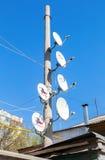 As antenas parabólicas montaram em um polo contra o céu azul Imagem de Stock