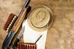 As armas da caça, folhas de papel da munição velhas, escrevem neles sua história Copie o espaço Zombaria acima imagem de stock