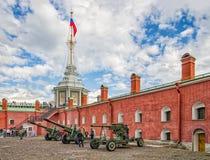 As armas da segunda guerra mundial nas paredes da fortaleza pela bandeira elevam-se Fotos de Stock Royalty Free