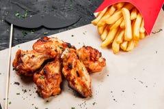 As asas de frango frito com batata fritam no papel do ofício no fundo preto fotos de stock