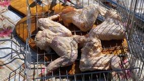 As asas de galinha cruas na grelha da grade estão na tabela na vila filme