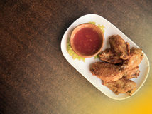 As asas de galinha fritaram no prato branco na tabela de madeira Imagem de Stock Royalty Free