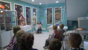 As atividades de extracurricular, menina que descreve a anatomia humana perto do esqueleto com grupo de crianças, texto aparecem  vídeos de arquivo