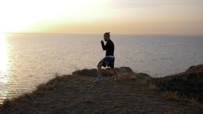 As atividades dos esportes, indivíduo muscular do pugilista cumprem sopros antes do campeonato no monte perto do mar filme