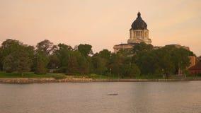 As aves aquáticas nadam o lago na frente da construção do capital de estado de South Dakota em Pierre SD video estoque