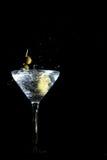As azeitonas em um toothpick deixaram cair em um vidro fotografia de stock royalty free