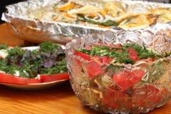 As bacias de vidro com saladas e bacia com folha de alumínio com pescadas postas de conserva com batatas e especiarias cozeram no Imagens de Stock Royalty Free