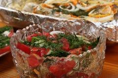 As bacias de vidro com saladas e bacia com folha de alumínio com pescadas postas de conserva com batatas e especiarias cozeram no Imagens de Stock