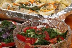 As bacias de vidro com saladas e bacia com folha de alumínio com pescadas postas de conserva com batatas e especiarias cozeram no Fotos de Stock Royalty Free