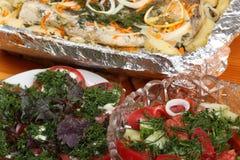 As bacias de vidro com saladas e bacia com folha de alumínio com pescadas postas de conserva com batatas e especiarias cozeram no Fotografia de Stock Royalty Free