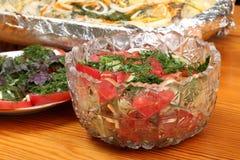 As bacias de vidro com saladas e bacia com folha de alumínio com pescadas postas de conserva com batatas e especiarias cozeram no Fotografia de Stock