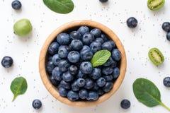 As bagas frescas saudáveis, os frutos e a salada verde folheiam no fundo branco Foto de Stock Royalty Free