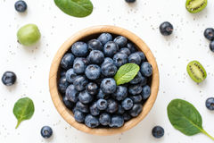 As bagas frescas saudáveis, os frutos e a salada verde folheiam no fundo branco Imagens de Stock