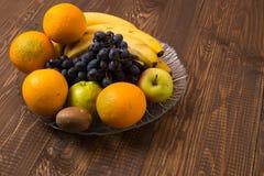 As bananas, laranjas, maçãs, uvas estão no prato Imagens de Stock