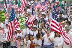 As bandeiras americanas da onda dos hispânicos como centenas de milhares de imigrantes participam em março para os imigrantes e o Imagens de Stock