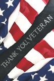 As bandeiras americanas perto da escrita de agradecem-lhe, veteranos Imagens de Stock