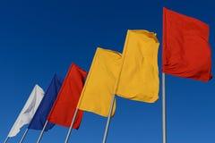 As bandeiras brancas, azuis, vermelhas e amarelas tornam-se no vento contra o céu fotografia de stock royalty free