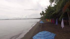 As bandeiras da bandeira e o parasol aéreas, coloridas do guarda-chuva alinham no Sandy Beach vazio tropical filme
