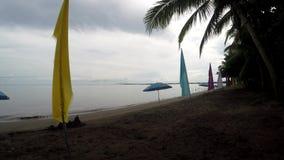 As bandeiras da bandeira e o parasol coloridos do guarda-chuva alinham no Sandy Beach vazio tropical filme
