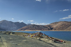 As bandeiras da estrada e da oração aproximam o lago nas montanhas Fotografia de Stock