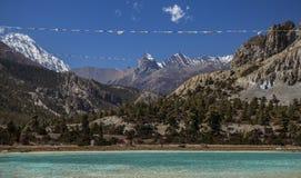 As bandeiras da oração sobre o lago da montanha no circuito de Annapurna arrastam, Nepa Imagem de Stock