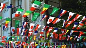 As bandeiras de países diferentes penduram em ruas da cidade vídeos de arquivo