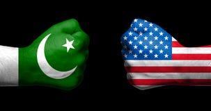 As bandeiras de Paquistão e de Estados Unidos pintados em dois apertaram o punho foto de stock royalty free