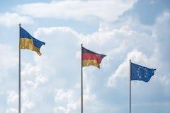As bandeiras de Ucrânia, de Alemanha e da União Europeia vibram no vento Imagens de Stock