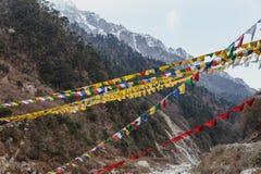 As bandeiras tibetanas da oração com a montanha preta com neve na parte superior são fundo no vale de Thangu e de Chopta no inver Fotos de Stock