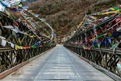 As bandeiras tibetanas da oração envolvidas com a ponte sobre o rio congelado com a montanha preta com neve na parte superior são Fotografia de Stock