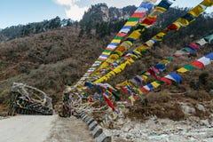 As bandeiras tibetanas da oração envolvidas com a ponte sobre o rio congelado com a montanha preta com neve na parte superior são Imagens de Stock Royalty Free