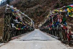 As bandeiras tibetanas da oração envolvidas com a ponte sobre o rio congelado com a montanha preta com neve na parte superior são Fotografia de Stock Royalty Free