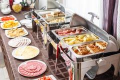 As bandejas do bufete calorosos aprontam-se para o serviço Café da manhã no smorgasbord do hotel Placas com alimento diferente foto de stock royalty free