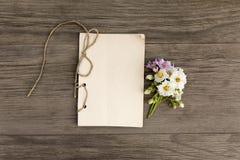 As batatas brancas e roxas florescem com o caderno feito a mão do ofício no fundo de madeira do grunge velho Vista superior minim fotografia de stock