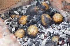 As batatas cozeram nos carvões na natureza imagens de stock