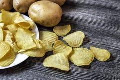 As batatas e os produtos da batata, fatias fritadas da batata, fatias da batata fritadas serrilhadas, fritaram flocos de batata e Imagem de Stock