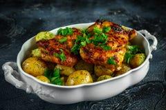 As batatas fervidas novas com aneto e manteiga serviram com as coxas de frango sem ossos skinless cozidas na caçarola do vintage foto de stock