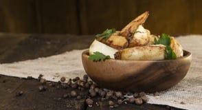 As batatas fritas, batata firmam em uma placa de madeira na tabela de madeira escura Foto de Stock Royalty Free