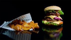 As batatas fritas e o hamburguer com queijo dobro e os verdes frescos no fundo preto e a reflexão no vidro surgem imagem de stock