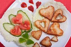 As batatas fritas e os legumes frescos desbastaram na forma de um coração imagem de stock