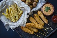 As batatas fritas fritadas, do ¡ de Ð cão e croquetes e batatas alaranjados da couve com molho e ketchup são decorados com legume fotos de stock royalty free