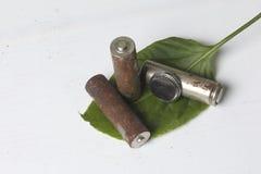 As baterias Waste de tipos diferentes são dispersadas Abaixo deles uma folha suculenta verde imagem de stock royalty free