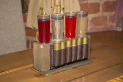 As bebidas alcoólicas em vidros de tiro estão no suporte com o cartr Fotografia de Stock