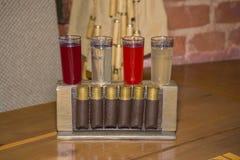 As bebidas alcoólicas em vidros de tiro estão no suporte com o cartr Fotos de Stock