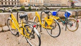 As bicicletas compartilhadas são alinhadas nas ruas de Grenoble Imagem de Stock