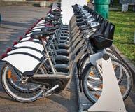 As bicicletas estão em seguido em um lugar de estacionamento em um arrendamento da bicicleta da cidade Fotografia de Stock Royalty Free