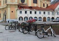 As bicicletas estacionaram na frente de uma igreja velha e de umas casas históricas - centro histórico de Bratislava, capital de  imagem de stock